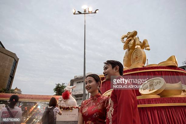 A golden statue of a goat is displayed for the upcoming Lunar New Year as a couple pose for a photograph in the Chinatown area of Bangkok on February...