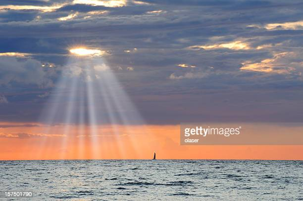 Golden sunbeam flowing over sailing ship and calm sea