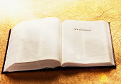 A copy of the Holy Bible, open to the beginning of the New Testament, lies defocused in golden sunbeams.