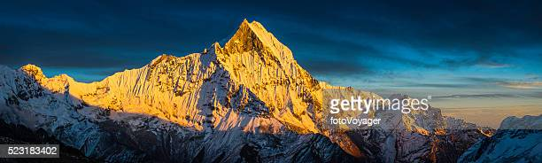 Golden sunlight on sacred mountain peak panorama Machapuchare Himalayas Nepal