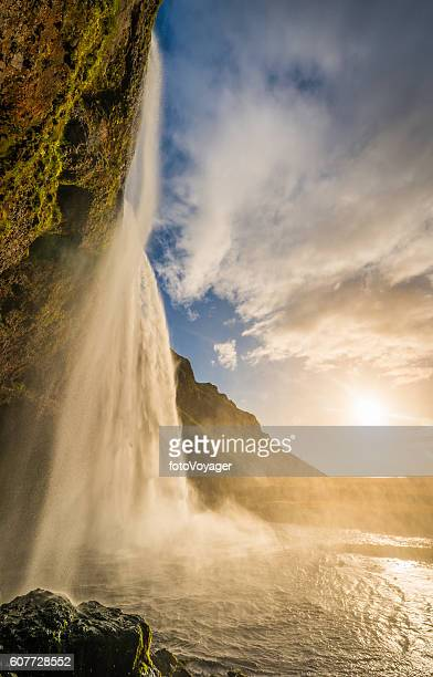 Golden sunset light illuminating mountain waterfall cascading over cliff Iceland