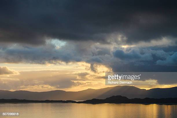 Golden sunset shining on Loch and clouds, over Raasay and Skye, Scotland. Taken from Wester Ross, near Applecross