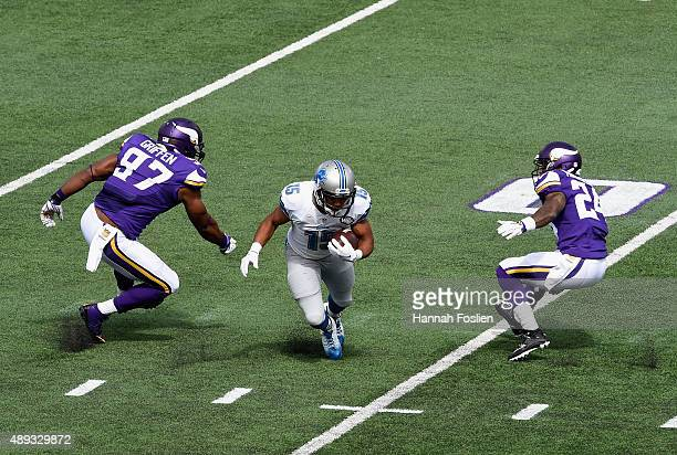 Golden Tate of the Detroit Lions carries the ball against Everson Griffen and Captain Munnerlyn of the Minnesota Vikings during the first quarter of...