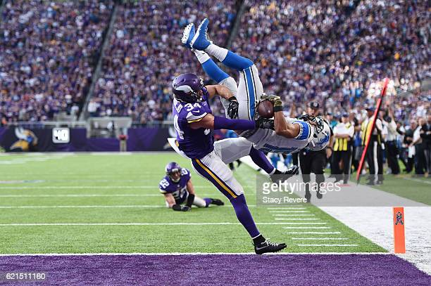 Golden Tate of the Detroit Lions leaps into the end zone for the go ahead touchdown while being tackled by Andrew Sendejo of the Minnesota Vikings...