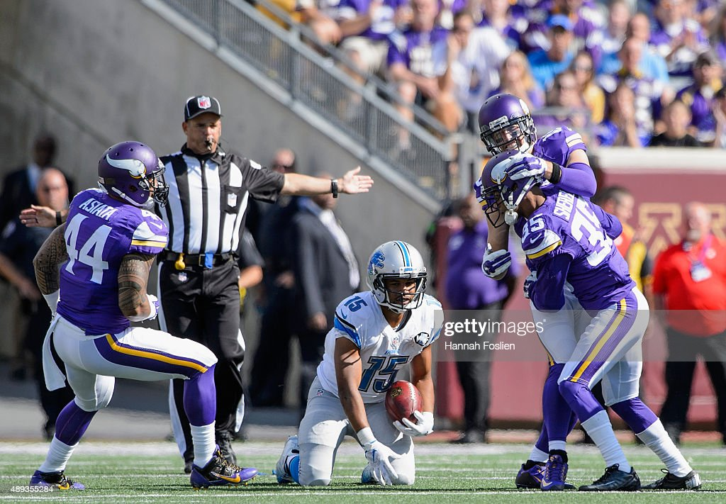 Golden Tate of the Detroit Lions reacts as Matt Asiata Marcus Sherels and Adam Thielen of the Minnesota Vikings celebrate a tackle on a punt return...