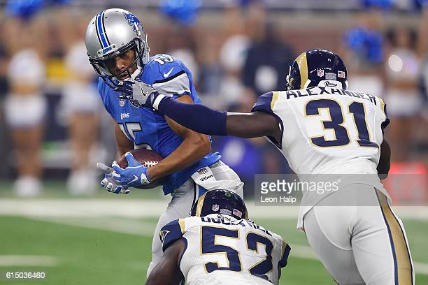 Golden Tate of the Detroit Lions runs the ball against Alec Ogletree of the Los Angeles Rams and Maurice Alexander during first quarter action at...