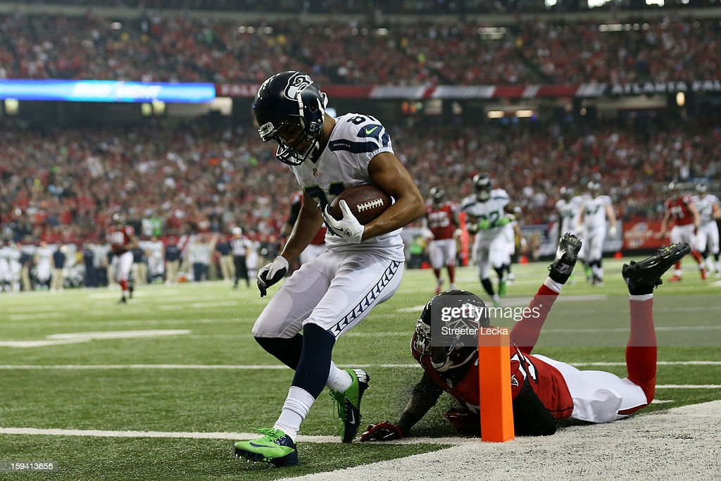 Golden Tate #81 of the Seattle Seahawks runs a reception in for a third quarter touchdown against the defense of Thomas DeCoud #28 of the Atlanta Falcons during the NFC Divisional Playoff Game at Georgia Dome on January 13, 2013 in Atlanta, Georgia.