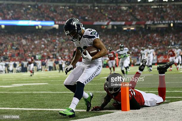 Golden Tate of the Seattle Seahawks runs a reception in for a third quarter touchdown against the defense of Thomas DeCoud of the Atlanta Falcons...