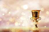 Golden trophy on wooden table, bokeh and glitter background with copy space