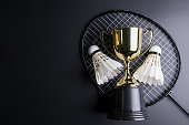 Golden trophy, Shuttlecocks and badminton racket on black background.Sport concept, Concept winner, Copy space image for your text
