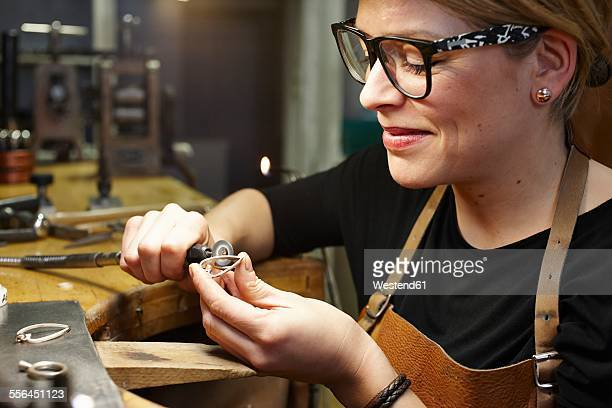 Goldsmith in workshop working on heart-shaped piece of jewelry