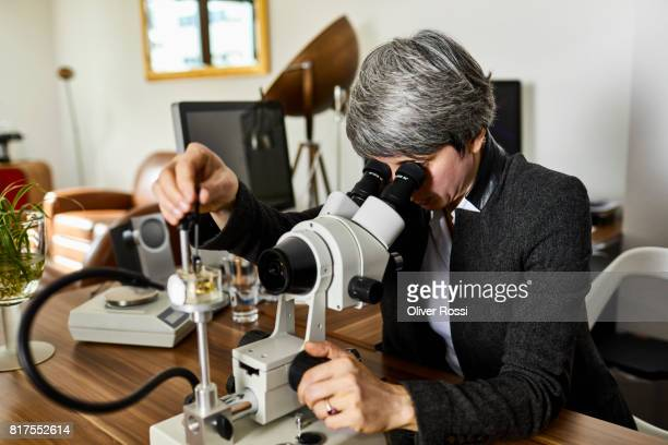 Goldsmith using a microscope in her workshop
