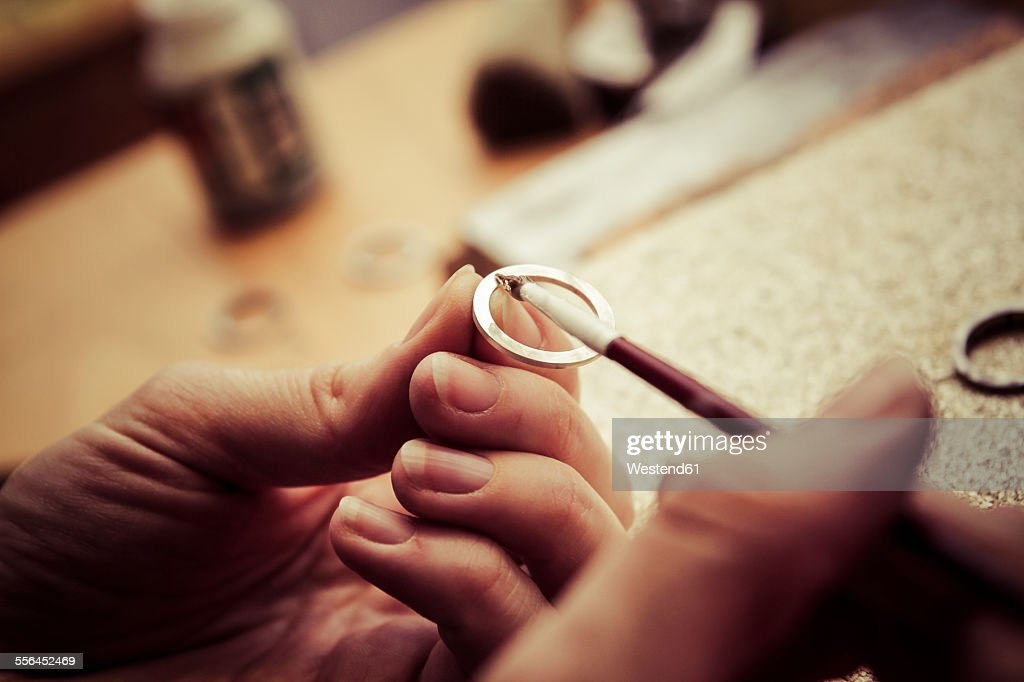 Goldsmith working on wedding rings, applying chemical on surface : Stock Photo