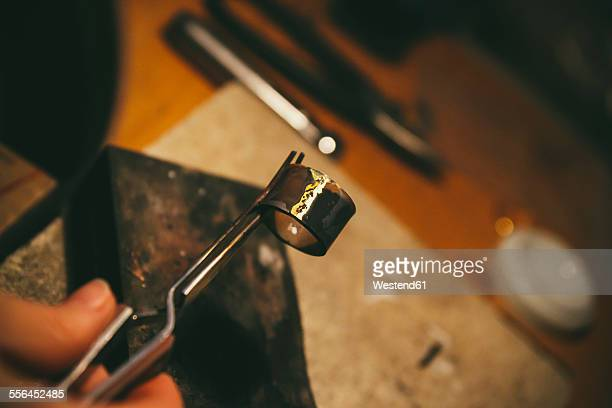 Goldsmith working on wedding rings, holding workpiece with forceps