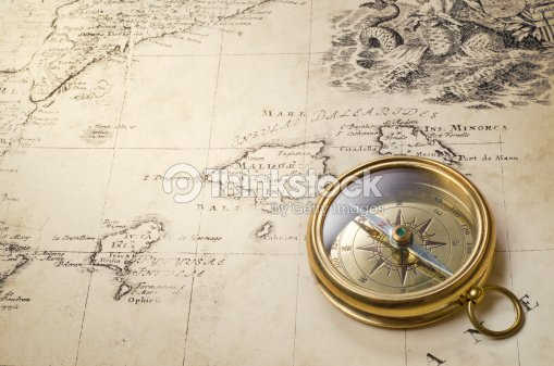 Goldtone compass laying on an old world map stock photo thinkstock goldtone compass laying on an old world map stock photo gumiabroncs Choice Image