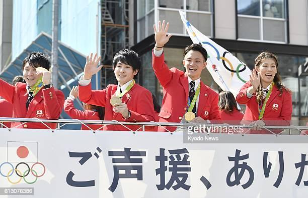 Goldwinning Japanese gymnasts Kohei Uchimura Ryohei Kato Yusuke Tanaka and the silverwinning female wrestler Saori Yoshida wave to spectators during...