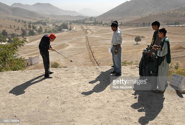 golf 10/04/06 KABUL AFGHANISTAN Naween hits from the tee box of the 1st hole a 371 yard Par 4 Looking on is resident Golf Pro and Club President...
