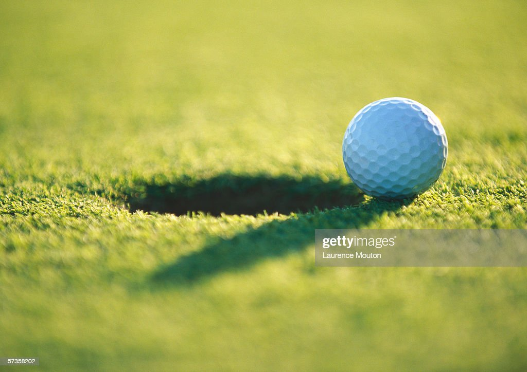 Golf ball at edge of hole, close-up