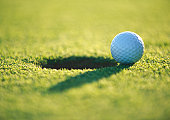 Golf ball at edge of hole, close-up