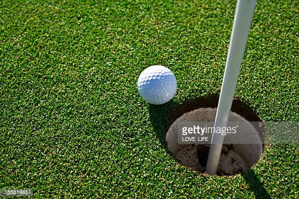 Golf ball at the edge of a hole on the green