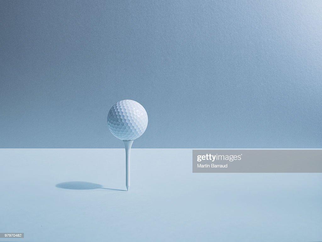 Golf ball balancing on tee : Stock Photo