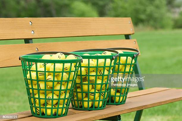 Golf ball baskets on bench