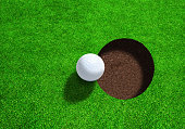 Golf ball close to hole as viewed from the top with copy space.