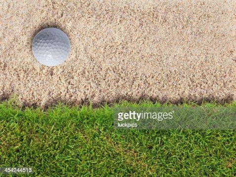 Golf ball in sand bunker near fresh green grass : Stock Photo