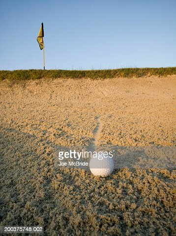 Golf ball in sand trap at sunrise, ground view