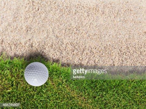 Golf ball on green grass near sand bunker : Stock Photo