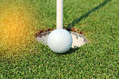 golf ball on lip of cup on green grass
