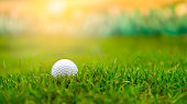 Golf ball on rough grass fairway on sunset