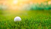 Golf ball on rough grass fairway on sunset