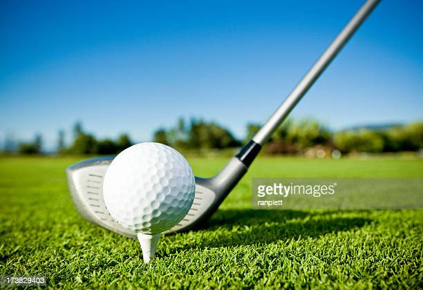 Golf ball on tee and golf club on golf course