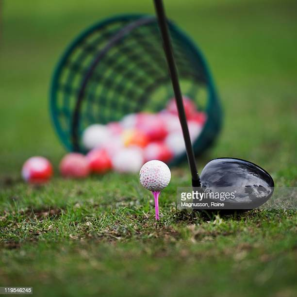 Golf ball on tee beside golf club