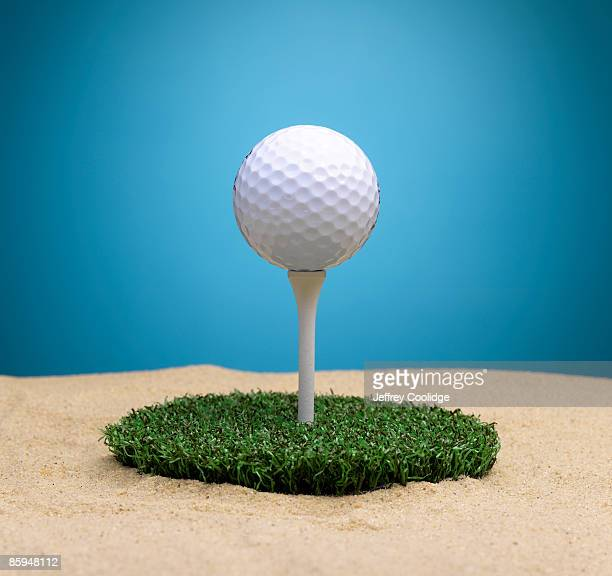 Golf Ball on Tee Surrounded By Sand Trap
