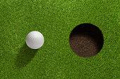 Golfball close to hole.