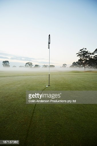 Golf ball rolling towards hole on course