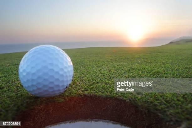 Golf ball sitting on edge of hole at sunset