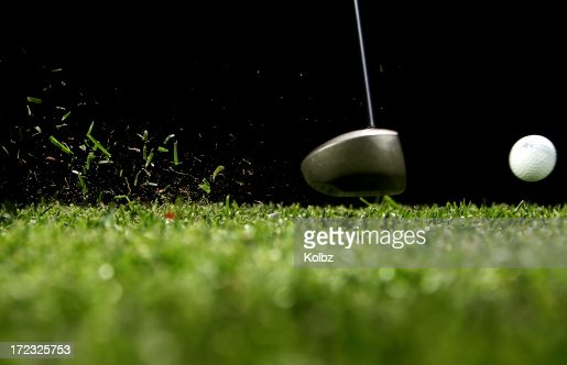 Golf ball struck by driver with black background
