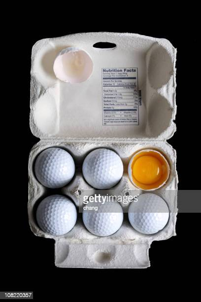 Golf Balls in Egg Carton with Broken One Showing Yolk