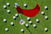 View from above of a golfballs on the green close to the hole with red flag.