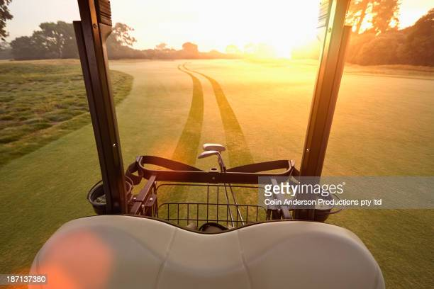 Golf cart making tracks on golf course