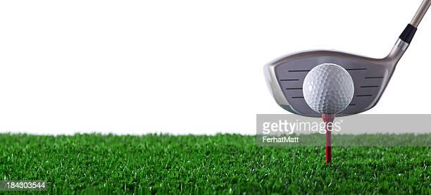 Golf club next to golf ball on red tee on grass