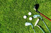 golf clubs and balls on grass