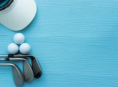 Golf clubs, golf balls, cap, on blue wooden table, with copy space.