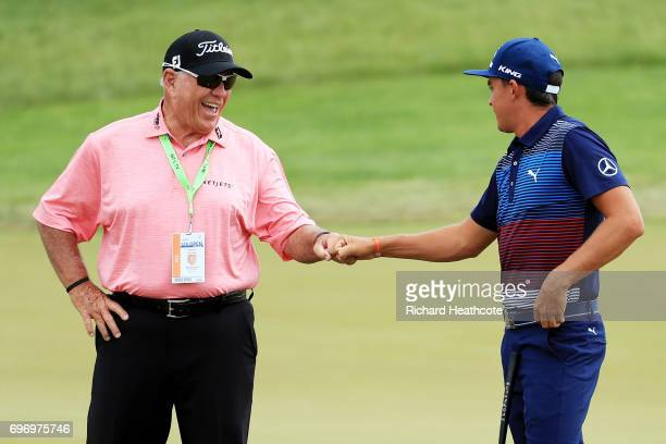 Golf coach Butch Harmon meets with Rickie Fowler of the United States on the practice green during the third round of the 2017 US Open at Erin Hills...