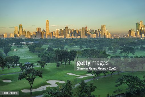 Golf Course And City Against Sky