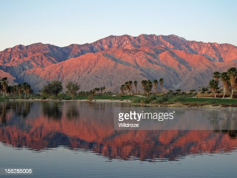 Golf course at dawn with sunrise kissed mountains