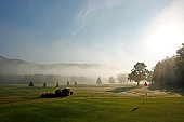 Golf course green with tractor and mowers